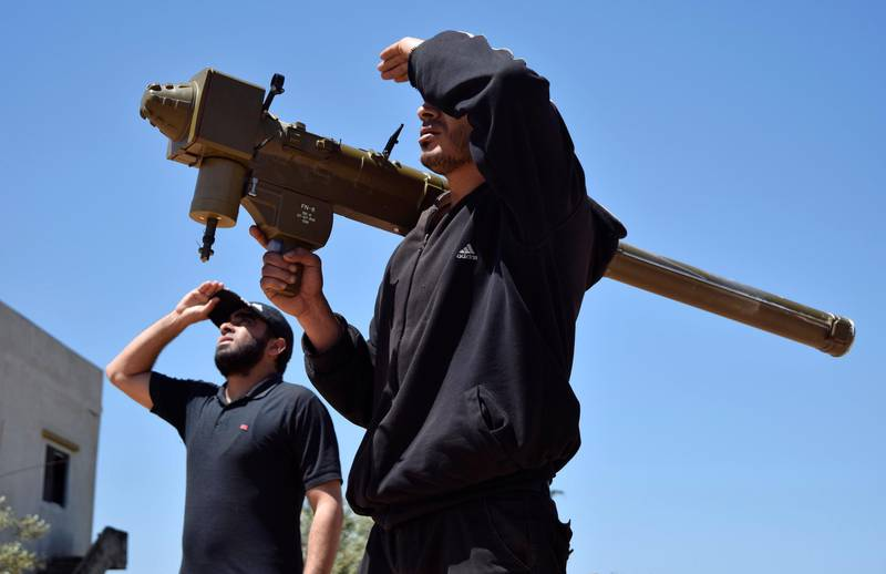 Rebel-fighters monitor the sky holding a FN-6 man-portable air-defence system (MANPADS) in the Syrian village of Teir Maalah, on the northern outskirts of Homs, on April 20, 2016. (Photo by MAHMOUD TAHA / AFP)