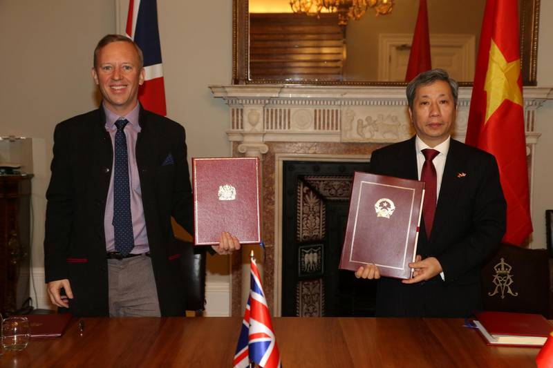 British Ambassador to Vietnam, Gareth Ward (L, front) and Vietnamese Ambassador to the UK, Tran Ngoc An show documents after they signed the UK-Vietnam Free Trade Agreement at the Foreign, Commonwealth and Development Office (FCDO) in London, Britain December 29, 2020. UK Government/Handout via REUTERS. ATTENTION EDITORS - THIS IMAGE HAS BEEN SUPPLIED BY A THIRD PARTY. NO RESALES. NO ARCHIVES.