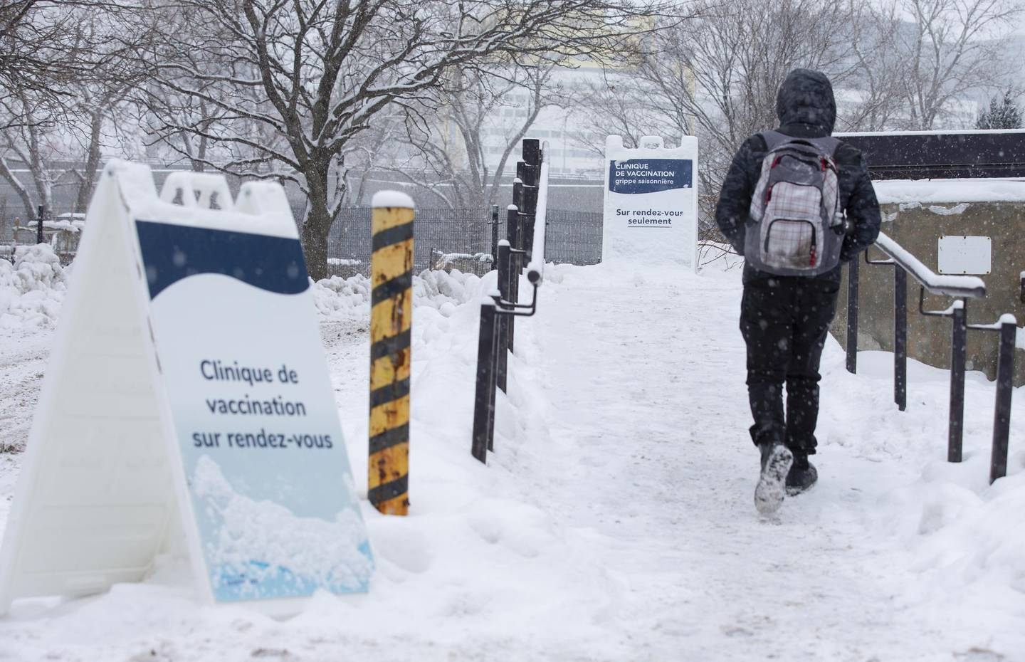 """A pedestrian walks past signs for a COVID-19 vaccination clinic in Montreal, Quebec, Canada, on Thursday, Jan. 21, 2021. Even though Canada has secured more vaccines per capita than any other nation, """"it doesn't mean much"""" when the bulk is not yet being delivered,an epidemiologist at the University of Toronto said. Photographer: Christinne Muschi/Bloomberg"""