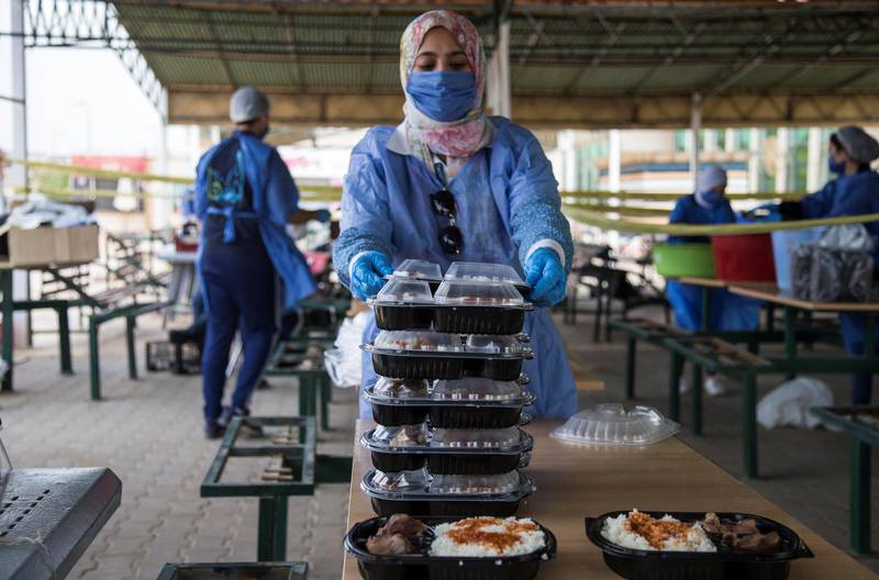epa08424491 Volunteers wearing face masks pack meals for poor people during the Muslims fasting month of Ramadan at 'LeBaladna' (for our country) charity organization, in Cairo, Egypt, 15 May 2020.  EPA-EFE/MOHAMED HOSSAM *** Local Caption *** 56088616