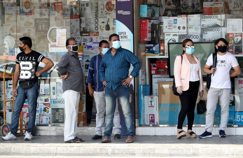 DUBAI, UNITED ARAB EMIRATES , June 11 – 2020 :- People wearing protective face mask during the hot and humid weather and waiting for the bus in Al Satwa area in Dubai. (Pawan Singh / The National) For News/Standalone/Online/Stock