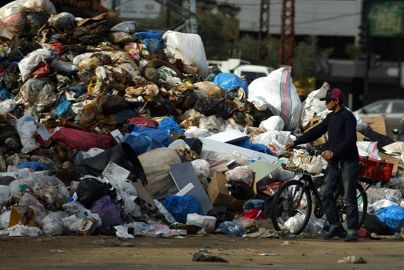 A man pushes his bicycle as he walks past a pile of garbage in the town of Jdeideh North East of the Lebanese capital Beirut, on January 2, 2016. (Photo by PATRICK BAZ / AFP)