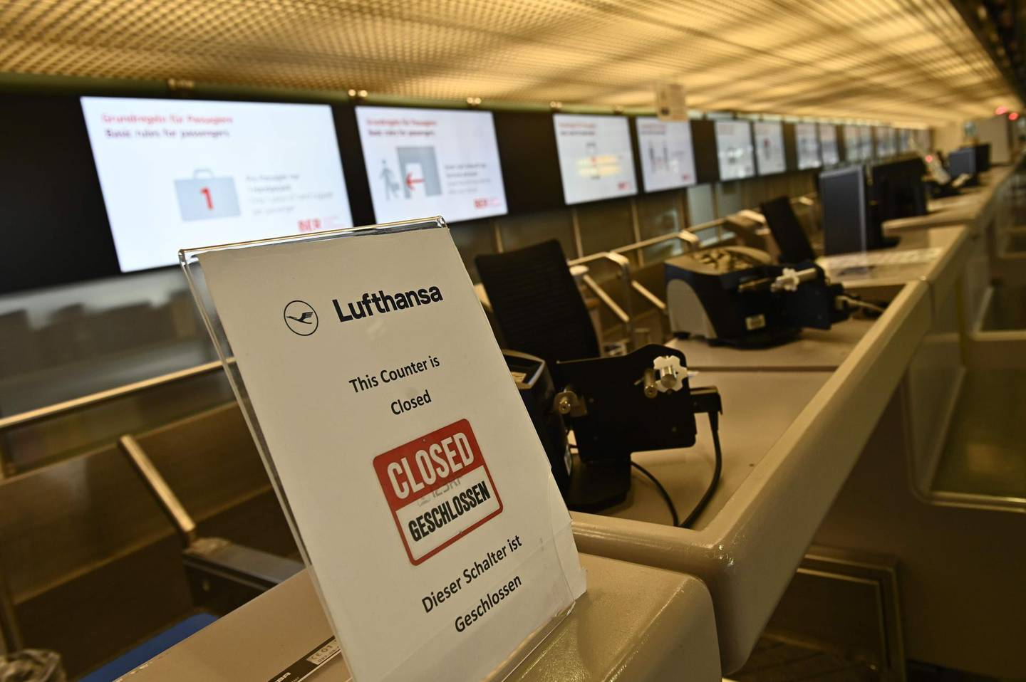 A closed check-in desk of German airline Lufthansa is seen at Berlin's Tegel airport on June 11, 2020. German airline Lufthansa said on June 11, 2020 that it would have to slash 22,000 full-time jobs as the recovery in demand for travel following the coronavirus pandemic will be muted. / AFP / Tobias SCHWARZ