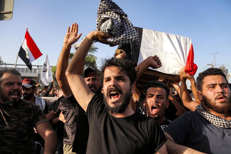 People chant slogans as they march with the body of renowned Iraqi anti-government activist Ihab al-Wazni (Ehab al-Ouazni) during a funerary procession in the central holy shrine city of Karbala on May 9, 2021 following his assassination. - Wazni, a coordinator of protests in the Shiite shrine city of Karbala, was a vocal opponent of corruption, the stranglehold of Tehran-linked armed groups and Iran's influence in Iraq. He was shot overnight outside his home by men on motorbikes, in an ambush caught on surveillance cameras. He had narrowly escaped death in December 2019, when men on motorbikes used silenced weapons to kill fellow activist Fahem al-Tai as he was dropping him home in Karbala, where pro-Tehran armed groups are legion. (Photo by Mohammed SAWAF / AFP)