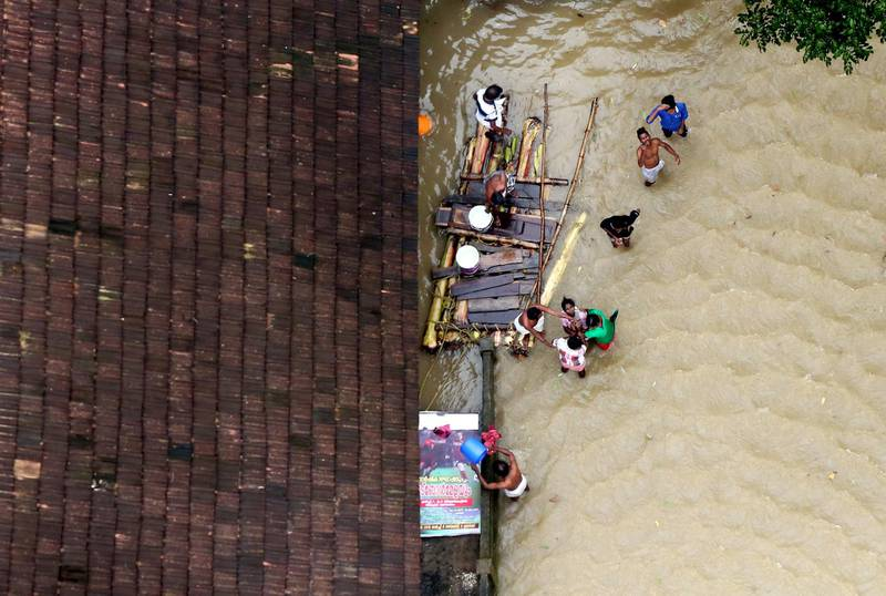 People wait for aid next to makeshift raft at a flooded area in the southern state of Kerala, India, August 19, 2018. REUTERS/Sivaram V