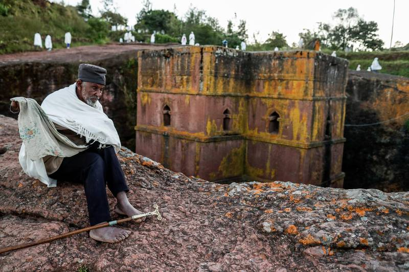 epa07922405 An elderly Ethiopian pilgrim sits in front of Saint George (or Bet Giyorgis) Church during Saint George's festival in Lalibela, Ethiopia, 04 October 2019 (issued 15 October 2019). The church of Saint George is one of eleven churches in Lalibela. The religious buildings were built at the height of medieval Ethiopian civilization from the ninth to the 12th century AD. The site of Lalibela is registered by UNESCO with the cultural inheritance of humanity since 1978. In order to protect the churches, roofs were installed above each of them except for the Church Saint Georges, which allows construction evacuation of water during heavy rains to minimize erosion.  EPA-EFE/STEPHANIE LECOCQ