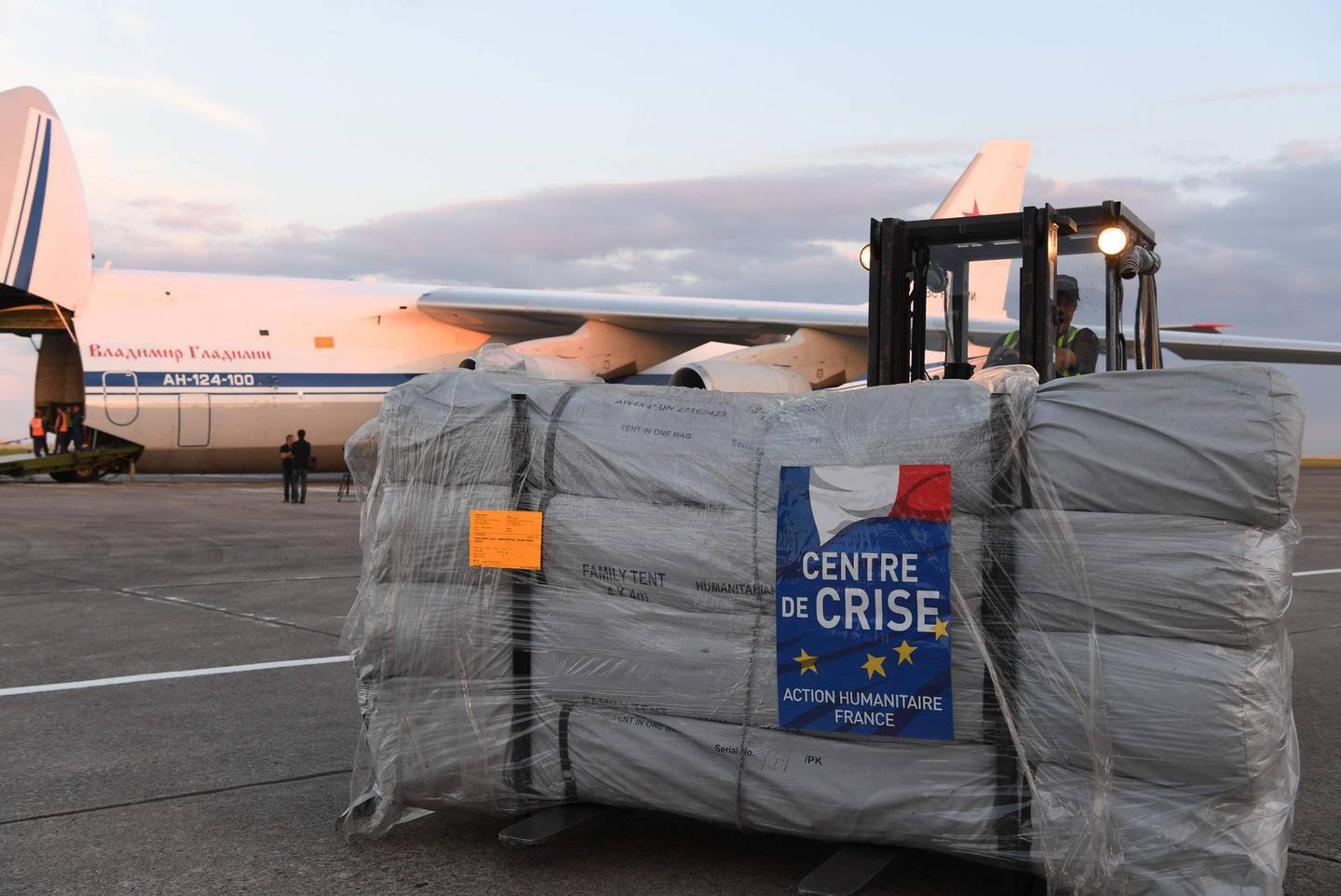 A forklift moves humanitarian supplies to be loaded onto Russian military officer stands by as an Antonov An-124 Ruslan - Widebody at the former Chateauroux-Deols Marcel Dassault Airport in central France on July 20, 2018.  France and Russia are jointly delivering humanitarian aid to the former Syrian rebel enclave of Eastern Ghouta, the French Presidency said in a statement with Russia on July 20. A Russian cargo plane arrived late in Chateauroux to load 50 tons of medical equipment and essential goods provided by France, said an AFP videographer at the scene, to be transported to the former rebel area which was recaptured by Syrian troops this Spring.  / AFP / Alain JOCARD