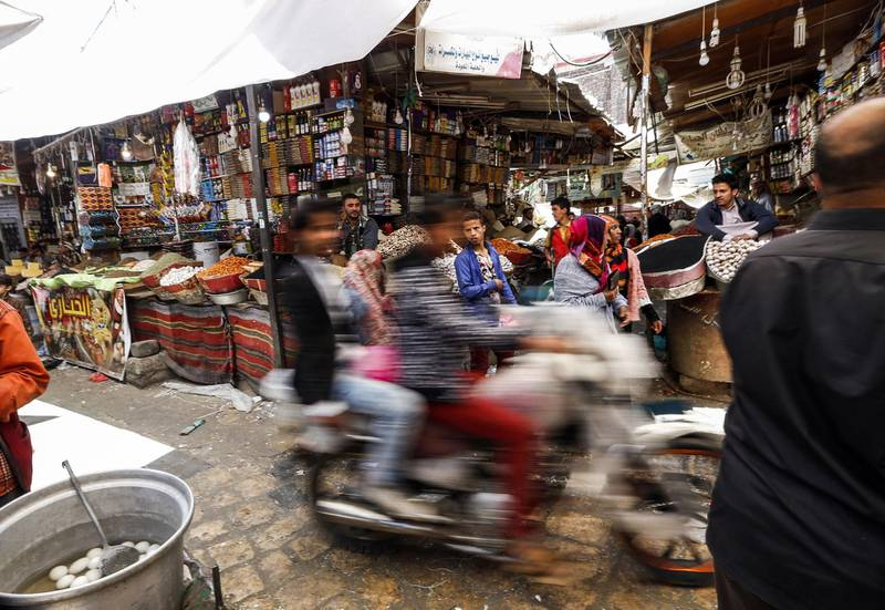 TOPSHOT - Yemenis ride in a motorcycle down an alley in the market in the old city of the capital Sanaa on February 15, 2018. / AFP PHOTO / MOHAMMED HUWAIS