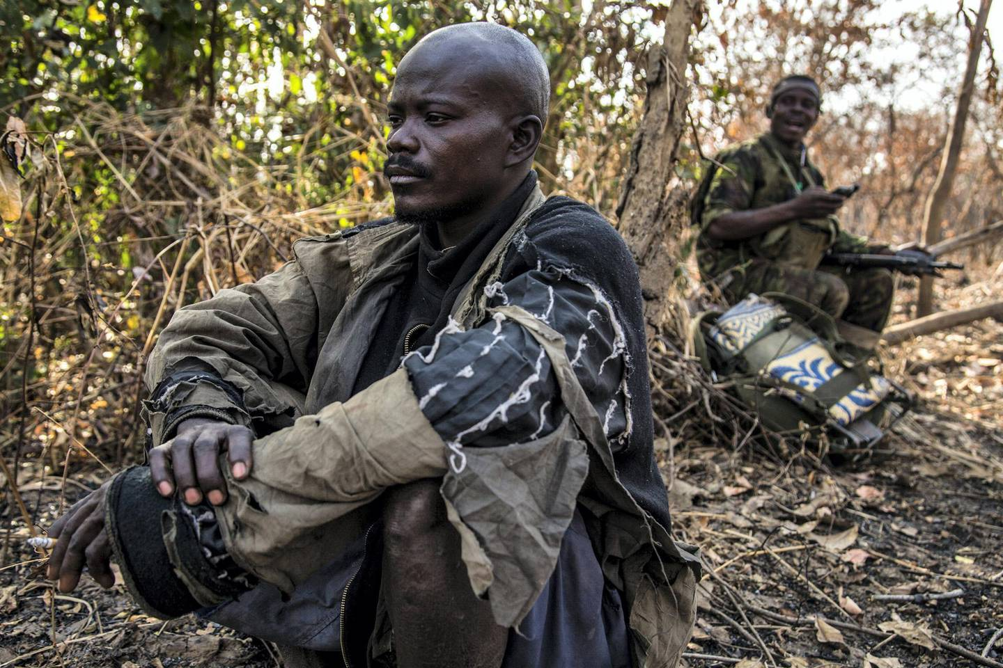"""A suspected poacher rests in the shade after being arrested, waiting to be taken to a holding cell. Constant - a father-of-one in his late 30s whose wife is pregnant with their second child - said hunting was the only way he could make ends meet for his family: """"There are no opportunities. I do this to survive."""" People living around the Chinko reserve are among the most marginalised and impoverished communities in the world."""