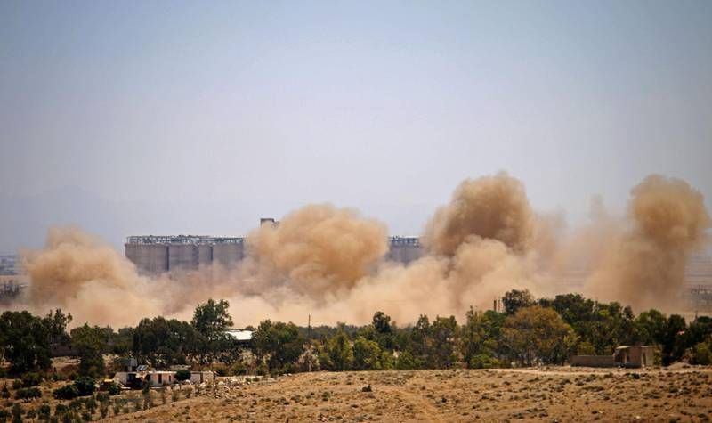 Smoke rises above eastern rebel-held areas of the city of Daraa during reported airstrikes by Syrian regime forces on July 8, 2018. Syrian army soldiers burned a rebel flag Saturday after they and Russian military police took over the crucial Nassib post on the border with Jordan. After launching a devastating offensive in Syria's southern region of Daraa on June 19, the forces of Damascus and Moscow were finally in charge of one of their main strategic targets -- the frontier crossing with Jordan. / AFP / Mohamad ABAZEED