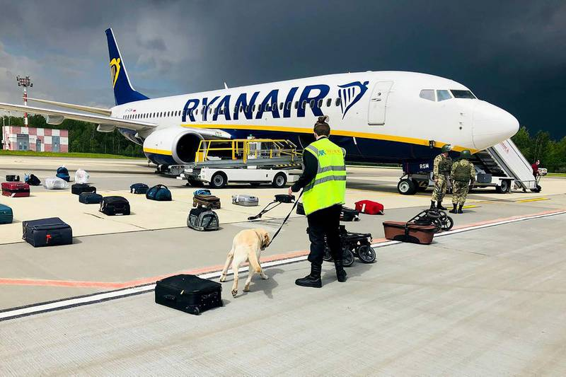 """TOPSHOT - A Belarusian dog handler checks luggages off a Ryanair Boeing 737-8AS (flight number FR4978) parked on Minsk International Airport's apron in Minsk, on May 23, 2021. Belarusian opposition Telegram channel Nexta said Sunday its former editor and exiled opposition activist Roman Protasevich had been detained at Minsk airport after his Lithuania-bound flight made an emergency landing. Protasevich was travelling aboard a Ryanair flight from Athens to Vilnius, which made an emergency landing following a bomb scare, TASS news agency reported citing the press service of Minsk airport. """"The plane was checked, no bomb was found and all passengers were sent for another security search,"""" Nexta said. """"Among them was... Nexta journalist Roman Protasevich. He was detained."""" - RESTRICTED TO EDITORIAL USE - MANDATORY CREDIT """"AFP PHOTO / ONLINER.BY """" - NO MARKETING - NO ADVERTISING CAMPAIGNS - DISTRIBUTED AS A SERVICE TO CLIENTS  / AFP / ONLINER.BY / - / RESTRICTED TO EDITORIAL USE - MANDATORY CREDIT """"AFP PHOTO / ONLINER.BY """" - NO MARKETING - NO ADVERTISING CAMPAIGNS - DISTRIBUTED AS A SERVICE TO CLIENTS"""