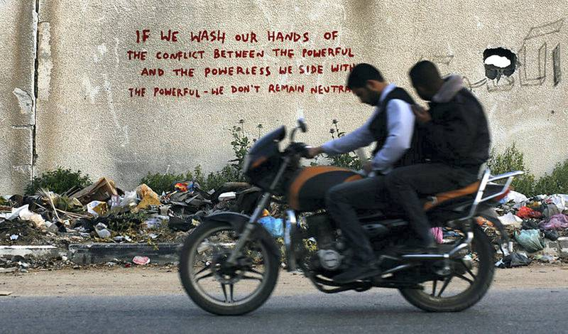 epa04699390 Palestinians ride a motorcycle past words presumably painted by British street artist Banksy on the wall of destroyed homes in Beit Hanun town in the northern Gaza Strip, 10 April 2015.  EPA/MOHAMMED SABER *** Local Caption *** 51882405