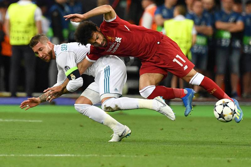 Liverpool's Egyptian forward Mohamed Salah (R) falls with Real Madrid's Spanish defender Sergio Ramos leading to Salah being injured during the UEFA Champions League final football match between Liverpool and Real Madrid at the Olympic Stadium in Kiev, Ukraine, on May 26, 2018. (Photo by GENYA SAVILOV / AFP)