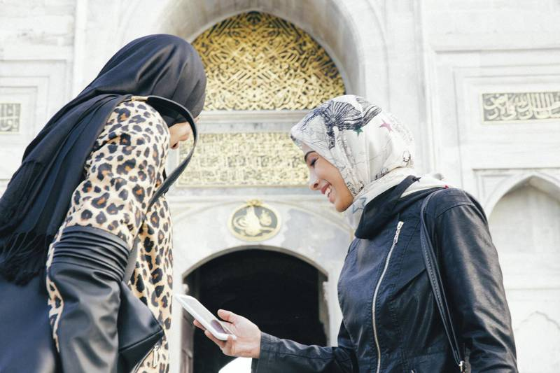 Cheerful tourist women looking at digital map in Istanbul, Turkey.