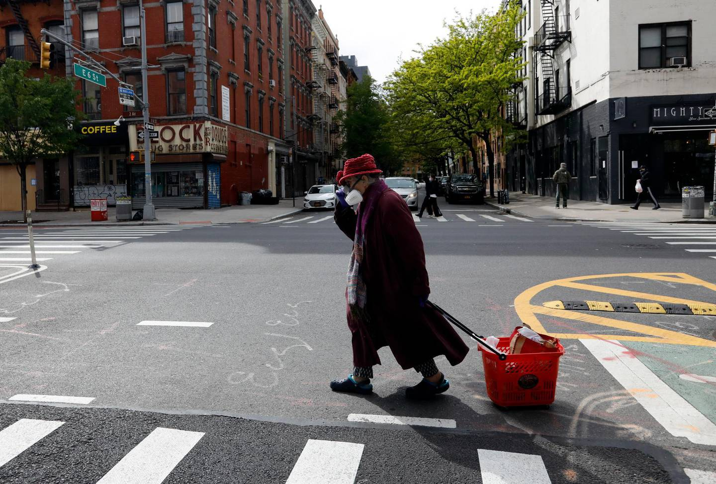 epa08412506 An elderly woman holds her hat as she wears a full face mask while crossing the street on the Lower East Side of New York, USA, 09 May 2020. New York City remains the epicenter of the coronavirus outbreak in the USA.  EPA/JASON SZENES