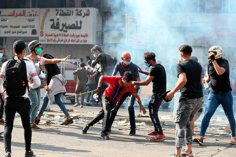 Protesters react to the tear gas fired by Iraqi security force during ongoing demonstrations, in Baghdad, Iraq, Tuesday, Nov. 12, 2019. (AP Photo/Hadi Mizban)