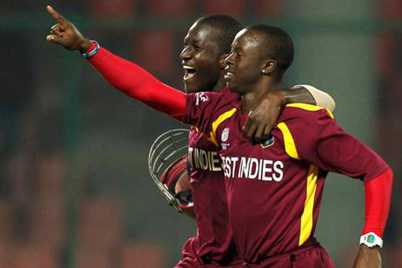 West Indies' Kemar Roach (R) celebrates taking a hat-trick after dismissing Netherlands' Berend Westdijk with his captain Darren Sammy during their ICC Cricket World Cup group B match in New Delhi February 28, 2011.  REUTERS/Adnan Abidi (INDIA - Tags: SPORT CRICKET)