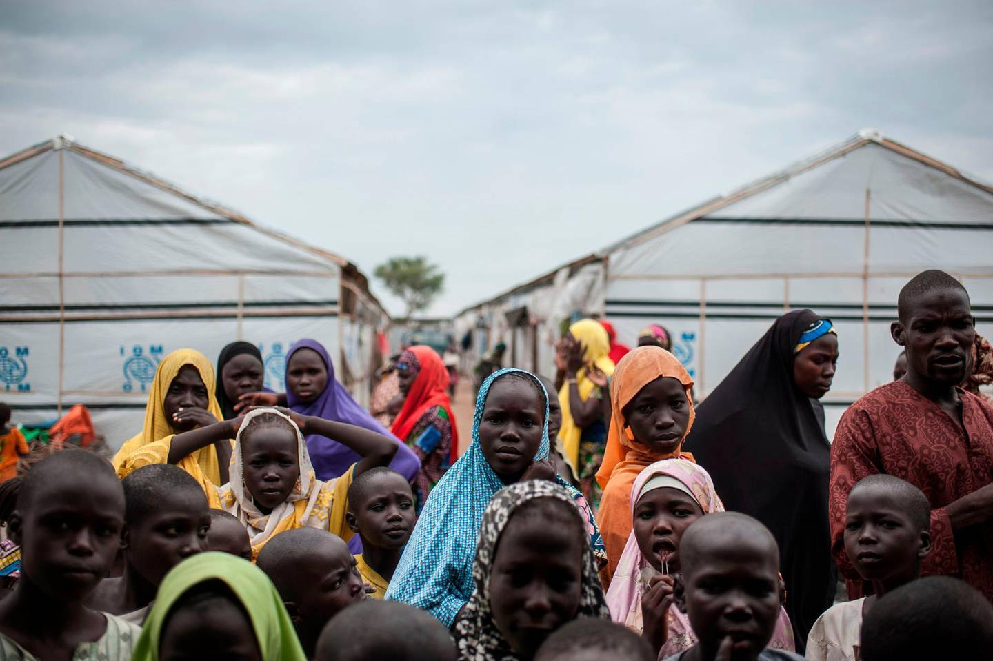 """TOPSHOT - People gather outside a tent in one of the IDP (Internally Displaced People) camps in Pulka on August 1, 2018. - As the presidential race heats up ahead of February polls, the Nigerian government and officials of Borno state, the epicentre of the Boko Haram Islamist insurgency, are encouraging and facilitating the """"return"""" of tens of thousands of people. As he campaigns for a second term in office, the incumbent president is working to show that he has delivered on his pledge to defeat the Islamists. But the reality is that people are being sent back to camps across Borno state while Boko Haram is still launching devastating attacks against military and civilian targets. Pulka is a garrison town built on a model becoming increasingly common across Nigeria's remote northeast region: a devastated town turned into a military base so soldiers can protect satellite camps and humanitarian agencies can distribute aid. (Photo by Stefan HEUNIS / AFP)"""