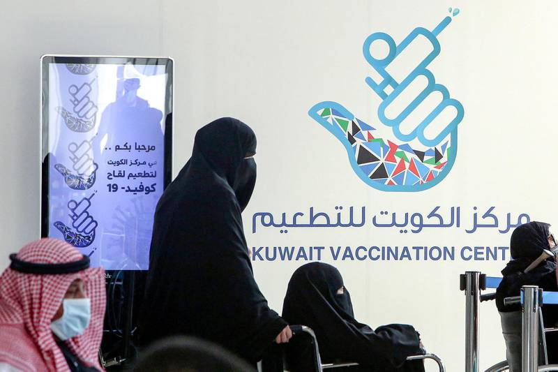 A woman pushes another in a wheelchair as they queue to register before receiving a dose of COVID-19 coronavirus vaccine at the make-shift vaccination centre erected at the Kuwait International Fairground, in the Mishref suburb south of Kuwait City on February 1, 2021.  Kuwait received on February 1 a shipment of 200,000 doses of Oxford-AstraZeneca vaccine. / AFP / YASSER AL-ZAYYAT