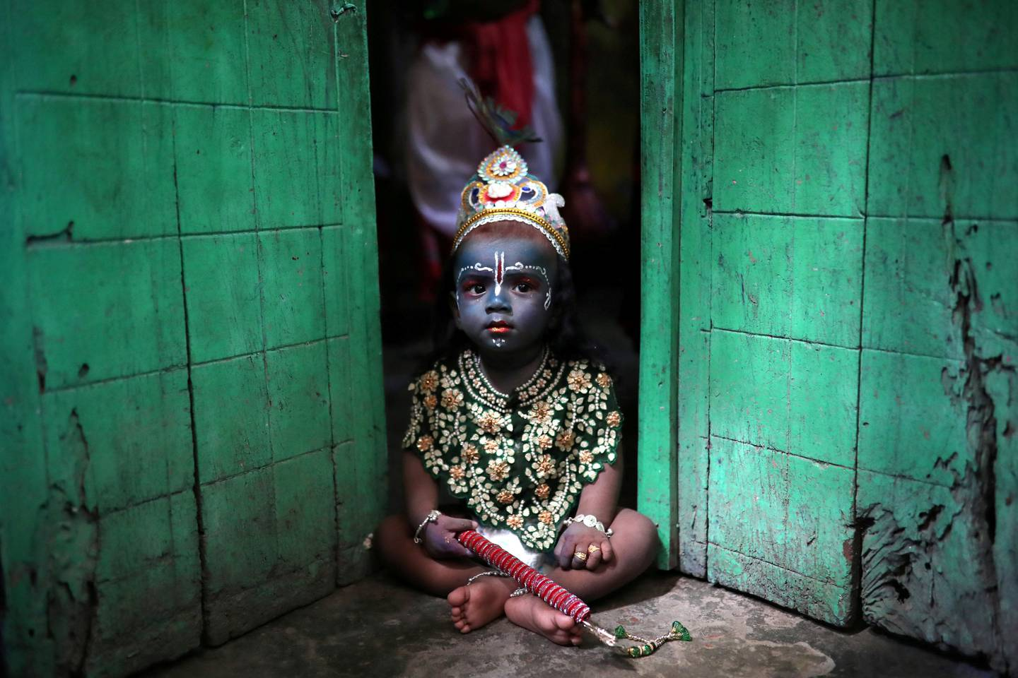 A child sits on a doorstep, dressed as Lord Krishna during Janmashtami festival, which marks the birth anniversary of Lord Krishna in Dhaka, Bangladesh, September 2, 2018. REUTERS/Mohammad Ponir Hossain      TPX IMAGES OF THE DAY