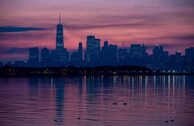 The skyline of Lower Manhattan is reflected in the water before sunrise on July 9, 2020 in New York City. / AFP / Johannes EISELE