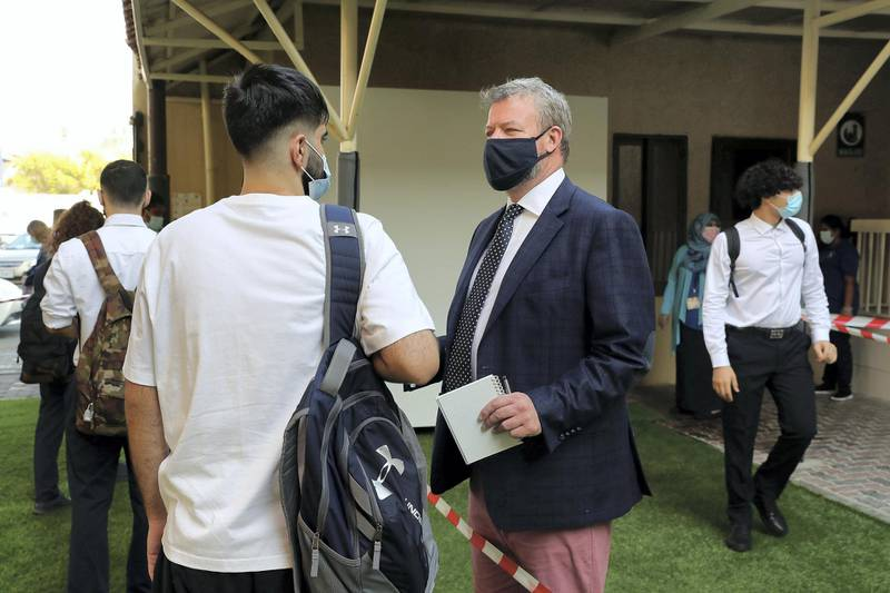 SHARJAH, UNITED ARAB EMIRATES , September 28 – 2020 :- Keith Sykes ,Principal (right) talking to the students on the first day of the school after reopening at the Victoria English School in Sharjah. New Covid safety setup placed in different areas of the school such as hand sanitizer, safety message, social distancing stickers pasted on the floor, disinfection tunnels installed at all the gates of the school. (Pawan Singh / The National) For News. Story by Salam