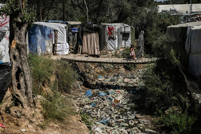 A woman with a child cross a wooden bridge in a improvised tents camp near the refugee camp of Moria in the island of Lesbos on June 21, 2020. - Greece's announcement that it was extending the coronavirus lockdown at its migrant camps until July 5, cancelling plans to lift the measures on June 22, coincided with World Refugee Day on June 27, 2020. (Photo by ARIS MESSINIS / AFP)