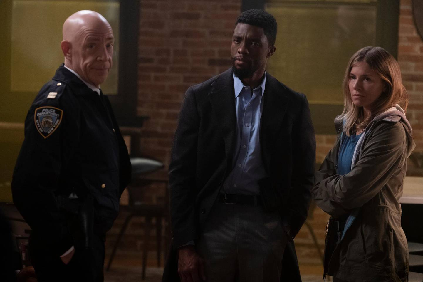 """This image released by STXfilms shows, from left, J.K. Simmons, Chadwick Boseman and Sienna Miller in a scene from """"21 Bridges,"""" in theaters on Nov. 22. (Matt Kennedy/STXfilms via AP)"""