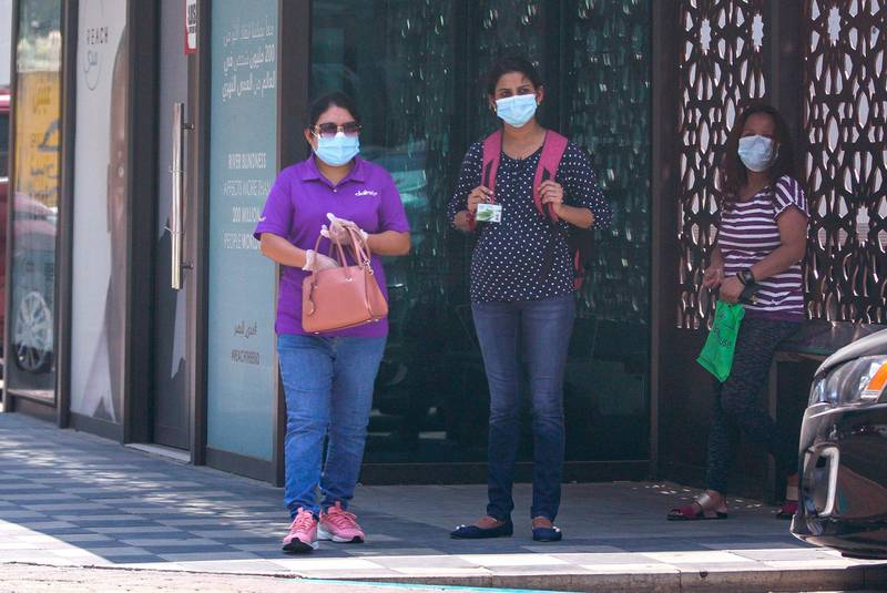 Abu Dhabi, United Arab Emirates, June 3, 2020.   Commuters at a bus stop protect themselves with face masks during the Covid-19 pandemic along Zayed the First Street.Victor Besa  / The NationalSection:  Standalone / Stock
