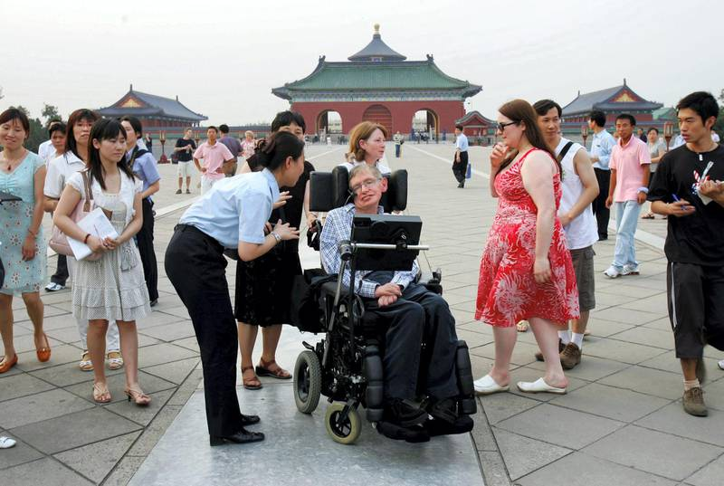 BEIJING - JUNE 18:  (CHINA OUT) A temple worker inquires of British scientist Stephen Hawking during his visit to the Temple of Heaven June 18, 2006 in Beijing, China. Hawking is visiting Beijing to attend the 2006 International Conference on String Theory, according to state media.  (Photo by China Photos/Getty Images)