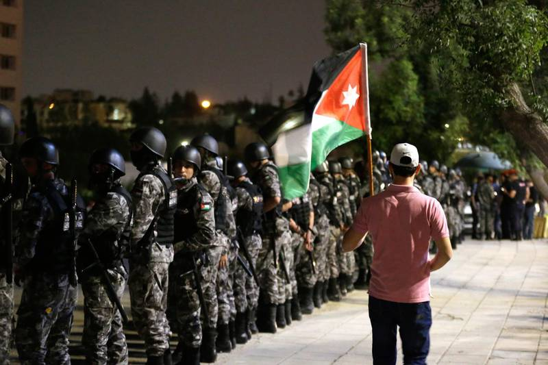 epa06792145 A protester holds a Jordanian national flag as security forces stand guard, during celebrations of the withdrawal of disputed tax reform, in Amman, Jordan, 08 June 2018. Reports state that al-Razzaz met on 06 June 2018 with members of the Parliament also Jordanian professional syndicates representatives and announced that the disputed new tax reform project would be withdrawn and other subjects of disagreement would be re-discussed. He was appointed on 04 June, following a week long protests against his predecessor's reforms. Protesters had taken to the streets to demand the withdrawal of the new taxes, the return to bread subsidy and a change in the country's economic policies.  EPA/ANDRE PAIN