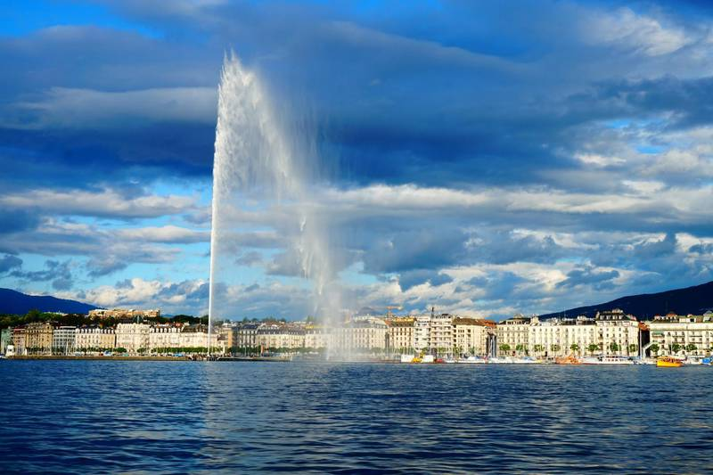 A view on the city of Geneva in the sunshine with clouds at dusk and the Jet d'Eau, located in the middle of Lake Geneva at the city of Geneva, Switzerland. The current Jet d'Eau was inaugurated in 1951. Reflections in the water.