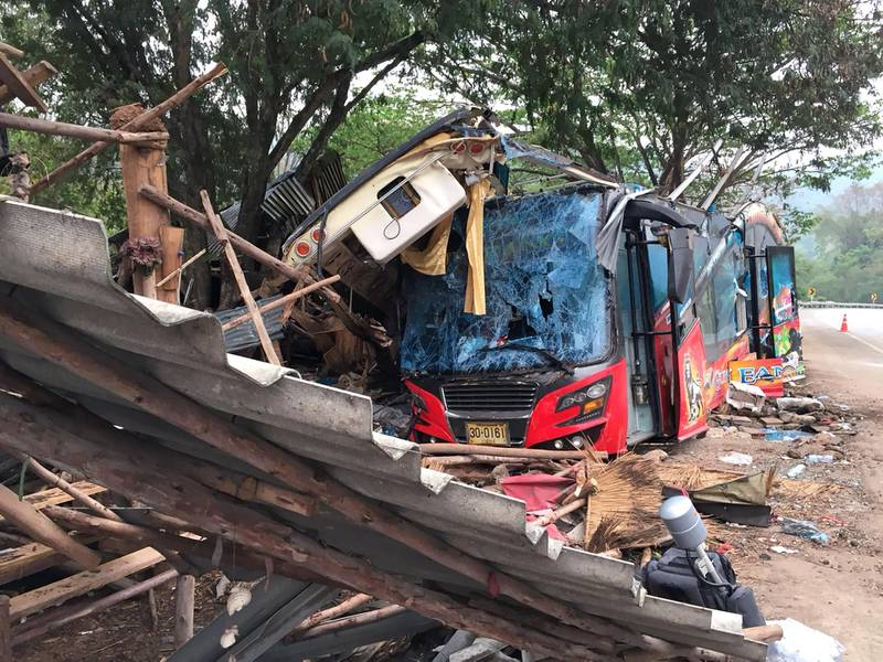 epa06619742 The wreckage of a tourist bus sits beside devastated roadside stalls at a crash site after an accident on a highway in Nakhon Ratchasima province, Thailand, 22 March 2018. The brakes on a tourist bus failed resulting in a crash with tractor trailer truck on a downhill curve at a highway of Nakhon Ratchasima northeastern province, killing 18 people and injuring 32, according to media reports.  EPA/STR THAILAND OUT