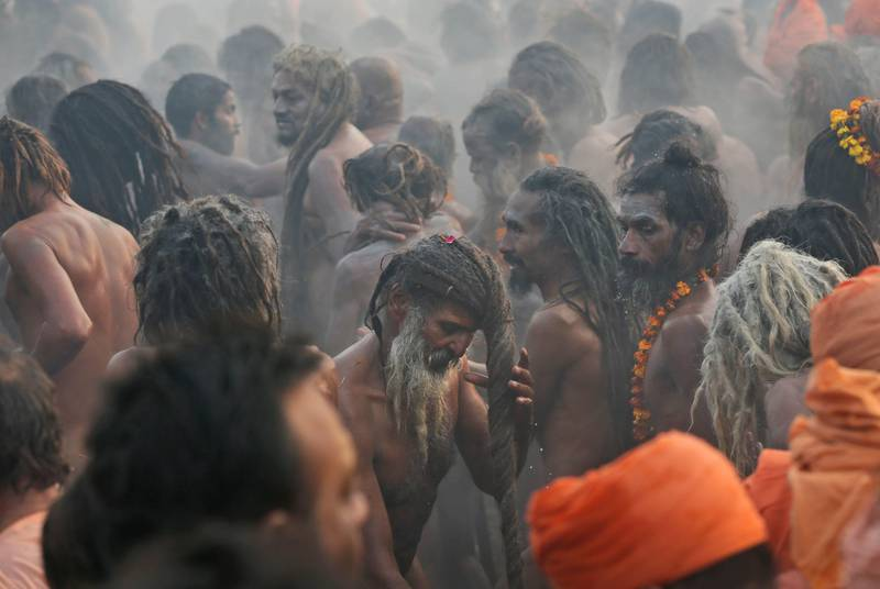 Naked Hindu holy men or a Naga Sadhus dry their hairs after a dip at Sangam, the confluence of the Rivers Ganges, Yamuna and mythical Saraswati on one of the most auspicious day Makar Sankranti,  the first day of the Maha Kumbh Mela, in Allahabad, India, Monday, Jan. 14, 2013. Millions of Hindu pilgrims are expected to take part in the large religious congregation of a period of over a month on the banks of Sangam during the Maha Kumbh Mela in January 2013, which falls every 12th year, where devotees wash themselves in the waters of the Ganges believing that it washes away their sins and ends the process of reincarnation. (AP Photo /Manish Swarup) *** Local Caption ***  India Maha Kumbh.JPEG-07a57.jpg