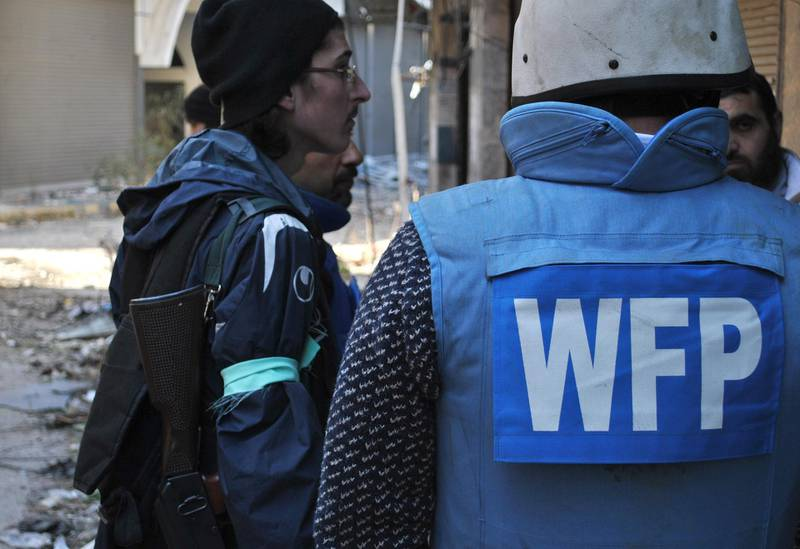 An United Nations World Food Programme (WFP) worker (R) talks with rebel fighters on February 8, 2014 on the second day of a humanitarian mission in a besieged district of the central city of Homs. The Syrian Red Crescent delivered a first batch of much-needed aid to civilians trapped for nearly two years in rebel-held areas of Homs city, despite coming under fire from mortars.  AFP PHOTO / BASSEL TAWIL (Photo by BASSEL TAWIL / BASSEL TAWIL / AFP)