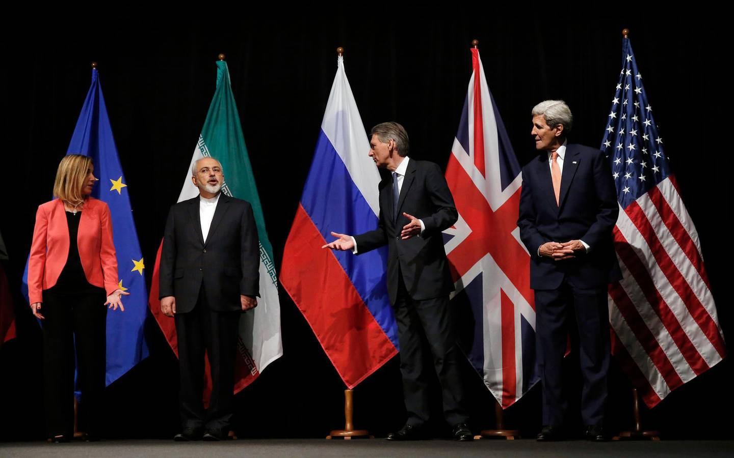 FILE - In this July 14, 2015 file photo, British Foreign Secretary Philip Hammond, 2nd right, U.S. Secretary of State John Kerry, right, and European Union High Representative for Foreign Affairs and Security Policy Federica Mogherini, left, talk to Iranian Foreign Minister Mohammad Javad Zarif as the wait for Russian Foreign Minister Sergey Lavrov, for a group picture in Vienna, Austria. President Hassan Rouhani is reportedly set to announce Wednesday, May 8, 2019, ways the Islamic Republic will react to continued U.S. pressure after President Donald Trump pulled America from Tehran's nuclear deal with world powers. (Carlos Barria, Pool Photo via AP, File)