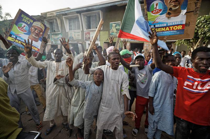 Supporters of President Muhammadu Buhari celebrate the announcement of results favoring his All Progressives Congress (APC) party in their state, anticipating victory, in Kano, northern Nigeria Monday, Feb. 25, 2019. Nigeria's electoral commission on Monday began announcing official results from the country's 36 states as President Muhammadu Buhari seeks a second term. (AP Photo/Ben Curtis)