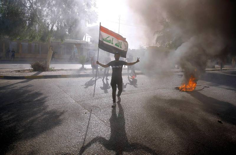 An Iraqi protester holds his national flag during a demonstration in Iraq's central holy shrine city of Najaf on June 8, 2020.  / AFP / STR