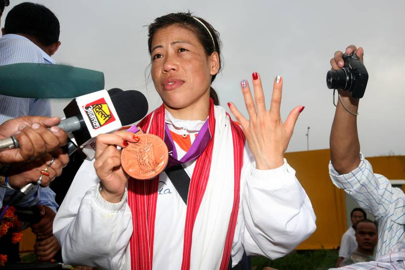 NEW DELHI, INDIA -  AUGUST 14 : London Olympics bronze medalist woman boxer Mary Kom is surrounded with her fans and media persons on her arrival at IGI Airport. Woman boxer Mary Kom was feted as India's latest sporting hero after the mother-of-two won a bronze medal at the London Olympics. (Photo by K Asif/India Today Group/Getty Images)