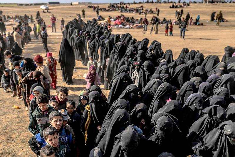Civilians evacuated from the Islamic State (IS) group's embattled holdout of Baghouz wait for bread and water at a screening area held by the Kurdish-led Syrian Democratic Forces (SDF), in the eastern Syrian province of Deir Ezzor, on March 5, 2019. - More than 7,000 people, mostly women and children, have fled the shrinking pocket over the past two days, as US-backed forces press ahead with an offensive to crush holdout jihadists. (Photo by Bulent KILIC / AFP)