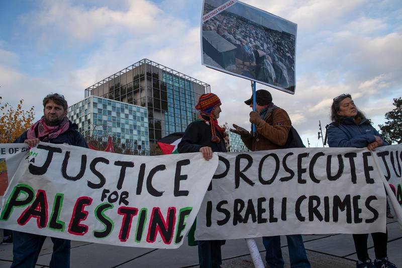 Demonstrators carry banners outside the International Criminal Court, ICC, rear, urging the court to prosecute Israel's army for war crimes in The Hague, Netherlands, Friday, Nov. 29, 2019. The ICC prosecutor was directed to reconsider her decision to not pursue charges in the Gaza Freedom Flotilla case. (AP Photo/Peter Dejong)