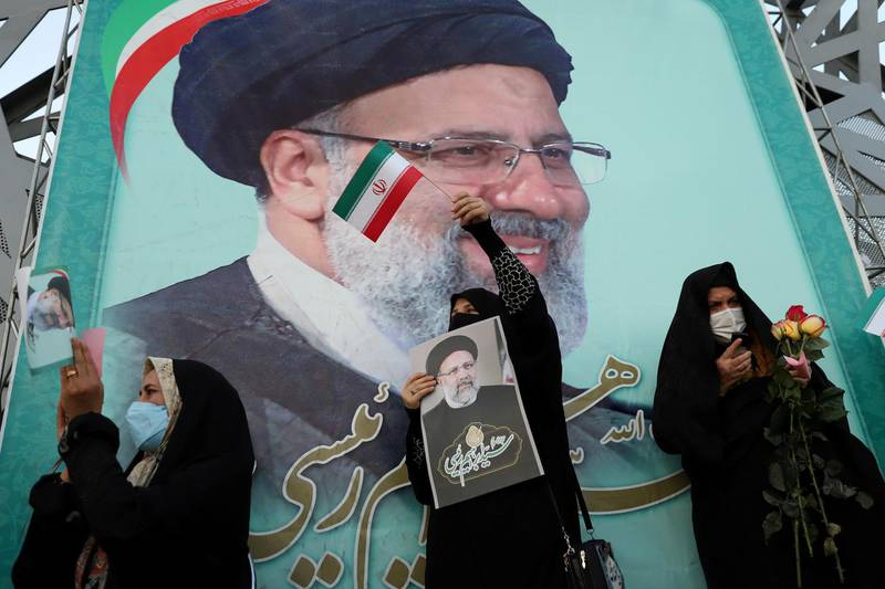 FILE PHOTO: A supporter of Ebrahim Raisi displays his portrait during a celebratory rally for his presidential election victory in Tehran, Iran June 19, 2021. Majid Asgaripour/WANA (West Asia News Agency) via REUTERS ATTENTION EDITORS - THIS IMAGE HAS BEEN SUPPLIED BY A THIRD PARTY./File Photo