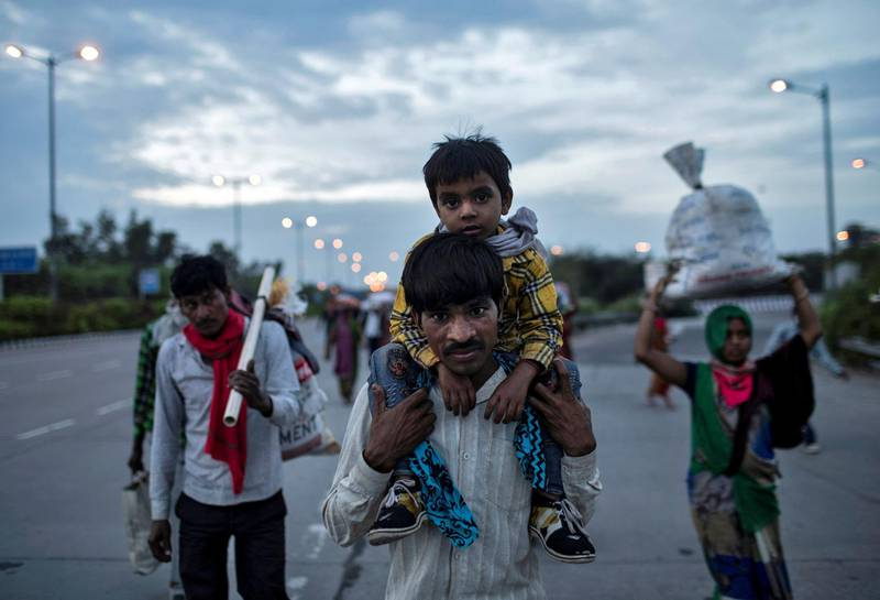 A migrant worker carries his son as they walk along a road with others to return to their village, during a 21-day nationwide lockdown to limit the spreading of coronavirus disease (COVID-19), in New Delhi, India, March 26, 2020. REUTERS/Danish Siddiqui     TPX IMAGES OF THE DAY