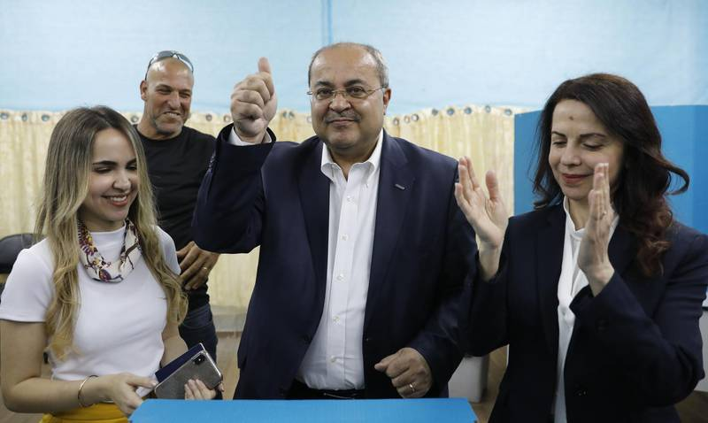 Israeli Arab politician Ahmed Tibi stands between his daughter (L) and wife as he casts his vote during Israel's parliamentary elections on April 9, 2019 in in the northern Israeli town of Taiyiba. Israelis voted today in a high-stakes election that will decide whether to extend Prime Minister Benjamin Netanyahu's long right-wing tenure despite corruption allegations or to replace him with an ex-military chief new to politics. / AFP / Ahmad GHARABLI