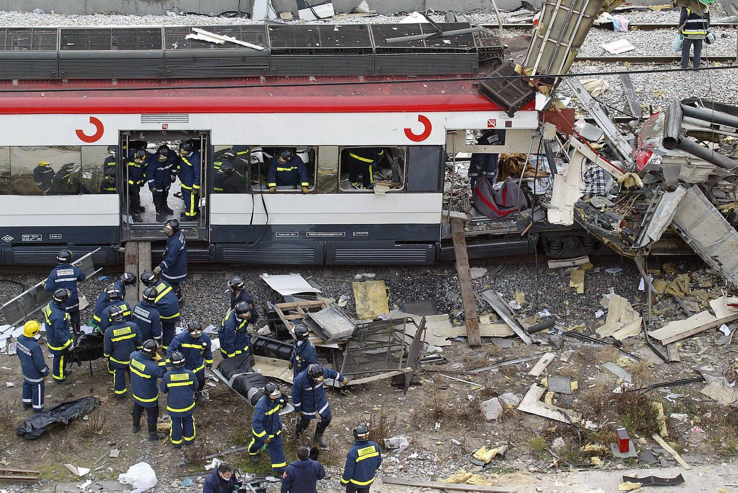 Bodies of victims are evacuated after a train exploded at the Atocha train station in Madrid 11 March 2004. At least 173 people were killed and some 600 injured early 11 March 2004 in near-simultaneous explosions on three trains in Madrid at the height of morning commuter traffic, the Spanish interior ministry said. In what appeared to be a deliberate attack staged only 72 hours ahead of Spanish general elections, the blasts went off on a long-distance high-speed carrier and two suburban trains packed with commuters. AFP PHOTO PIERRE-PHILIPPE MARCOU (Photo by PIERRE-PHILIPPE MARCOU / AFP)