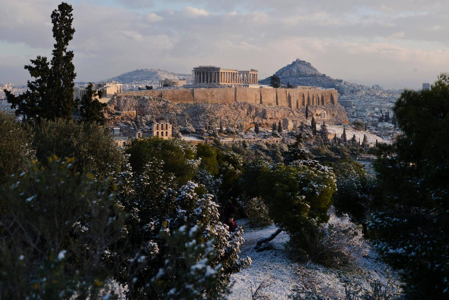 A man walks at Filopappos hill as at the background is seen the ancient Acropolis hill with the 500BC Parthenon temple, after a snowfall in Athens , on Tuesday, Jan. 8, 2019. (AP Photo/Petros Giannakouris)