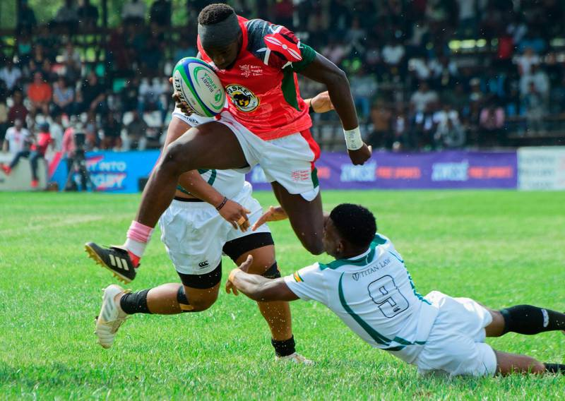 TOPSHOT - Kenya's fly-half Isaac Adimo (C) vies with Zimbabwe's Lenience Tamwera (R) during the 2018 Rugby African Gold Cup match between Kenya and Zimbabwe in Nairobi on June 30, 2018, which acts a qualifier for the 2019 Rugby World Cup in Japan. Kenya won the match 45-36. / AFP / KEVIN MIDIGO