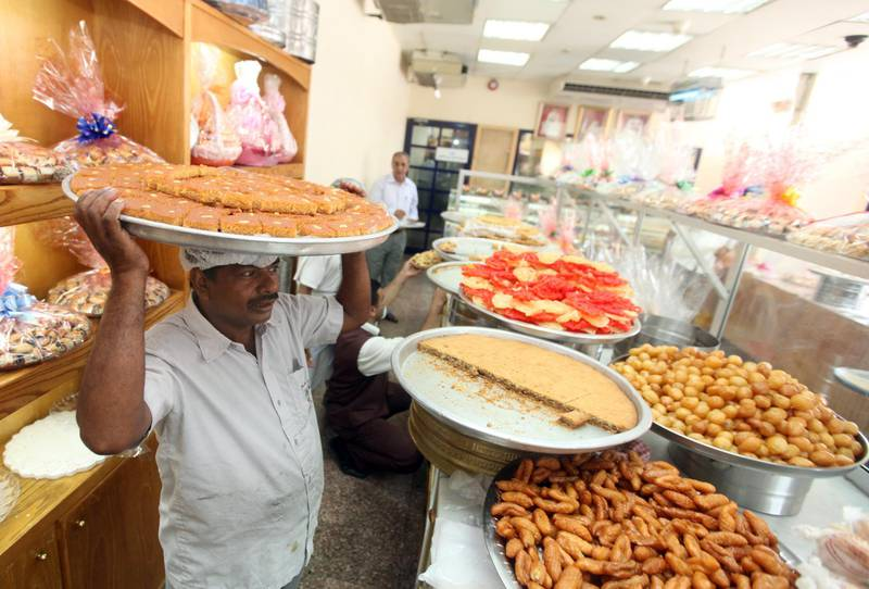 September 9, 2010/  Abu Dhabi /  Abdul Sharafudeen from the Al Saada Bakery brings out freshly backed arabic sweets to be sold the day before Eid-al-Fitr on of the busiest day of the year for the bakery September 9, 2010. (Sammy Dallal / The National)