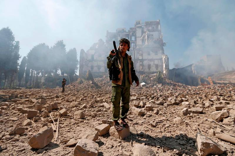 Huthi rebel fighters inspect the damage after a reported air strike carried out by the Saudi-led coalition targeted the presidential palace in the Yemeni capital Sanaa on December 5, 2017. Saudi-led warplanes pounded the rebel-held capital before dawn after the rebels killed former president Ali Abdullah Saleh as he fled the city following the collapse of their uneasy alliance, residents said. / AFP PHOTO