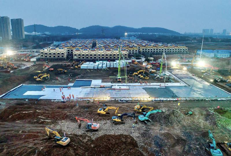 Excavators and workers are seen at the construction site where the new Huoshenshan Hospital is being built to treat patients of a new coronavirus on the outskirts of Wuhan, China January 27, 2020. Picture taken January 27, 2020. China Daily via REUTERS ATTENTION EDITORS - THIS IMAGE WAS PROVIDED BY A THIRD PARTY. CHINA OUT.
